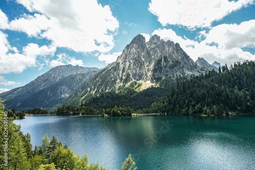 Panoramic view of Sant Maurici lake with Els Encantats peaks in the National Park of Aiguestortes, Lleida, Pyrenees, Catalonia