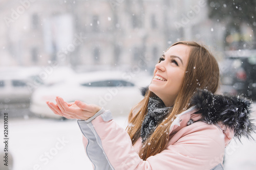Fotografija  Happy young woman catches snowflakes with his hands