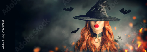 Halloween. Sexy witch portrait. Beautiful young woman in witches hat with long curly red hair over spooky dark magic forest background