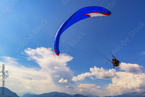 2018-08-23, Saint-Vincent-les-Forts, France. Tandem paragliders fly with beautiful clouds on the background.