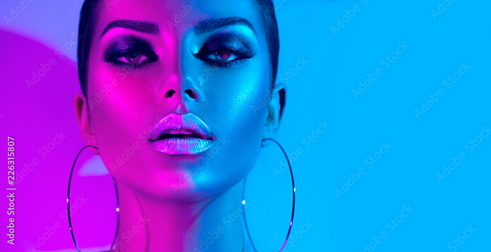 Fashion model brunette woman in colorful bright neon lights posing in studio. Beautiful sexy girl, trendy glowing makeup, metallic silver lips
