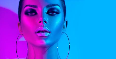 Fashion model brunette woman in colorful bright neon lights posing in studio....