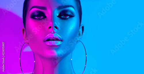 Obraz Fashion model brunette woman in colorful bright neon lights posing in studio. Beautiful sexy girl, trendy glowing makeup, metallic silver lips - fototapety do salonu