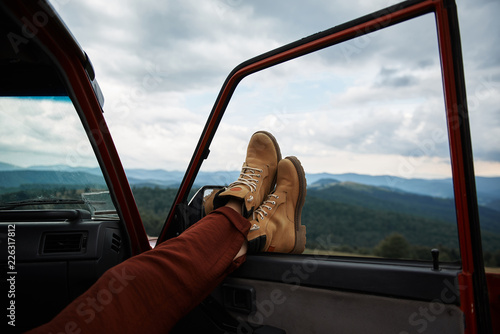 Fotografie, Tablou  Close up of feet of a relaxed traveler holding them on the window while enjoying