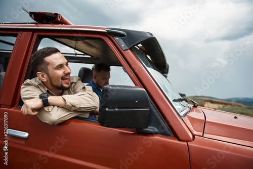 Garden Poster Brown Cheerful handsome young man sitting in the off-road car while travelling with his friend
