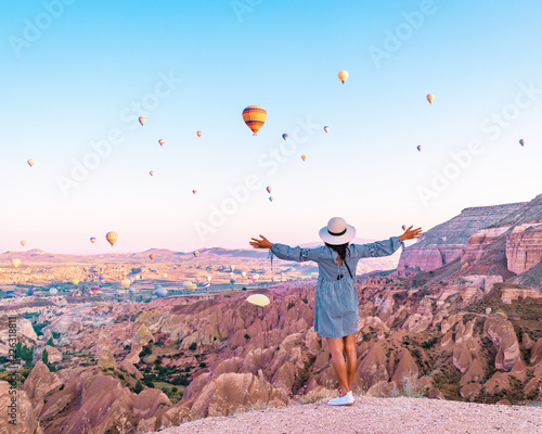 Turkey balloons Cappadocia Goreme Kapadokya , Sunrise in the mountains of Capadocia, happy young woman watching sunrise Wall mural