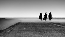 Silhouette Of Fishermen Returning From Their Fishing Spot In A Concrete Sea Pier On A Windy Late Afternoon In A Sand Cloud, Black And White Photo, Figueira Da Foz, Portugal.