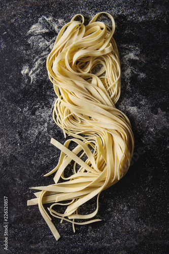 Variety of italian homemade raw uncooked pasta spaghetti and tagliatelle with semolina flour over black texture background. Flat lay, space