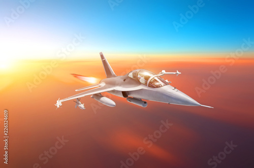Fotomural Supersonic fighter with arms flies in the sky at sunset with afterburner of engines