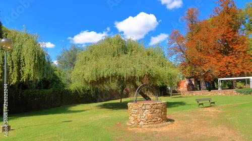 Paisaje soleado de parque con pozo y arboles en Benavente, Zamora, España