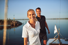 Smiling Young Woman Standing With Her Husband On Their Yacht