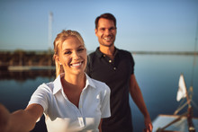 Young Couple Smiling While Standing Together On Their Yacht
