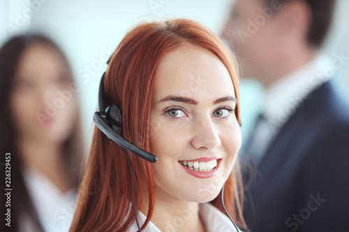 Papiers peints Akt Portrait of a smiling creative businesswoman with earpiece in office