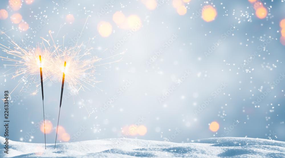 Fototapeta zwei brennende wunderkerzen im schnee