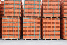 Stacks Of New, Red Ceramic Brick Stacked On Wooden Pallets.