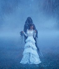 Dark Lord's Bride In White Vintage Mesh Translucent Dress And A Silver Necklace Is Standing On The Frozen Grass In A Thick Blue Fog In Dementor Hands. Halloween Costume Idea. Art Photo Harry Potter