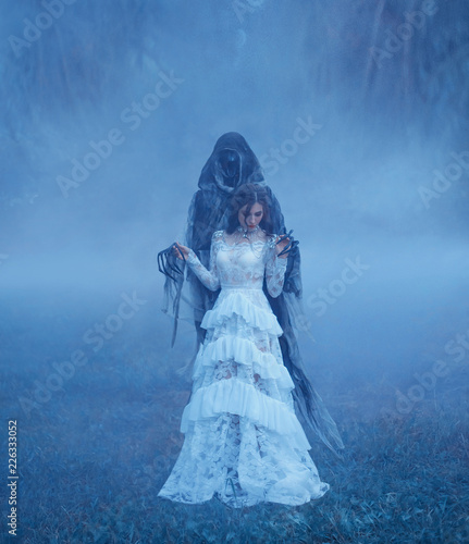 Canvas-taulu Dark Lord's Bride in white vintage mesh translucent dress and a silver necklace is standing on the frozen grass in a thick blue fog in Dementor hands