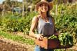 Leinwandbild Motiv Woman harvesting fresh vegetables from her farm
