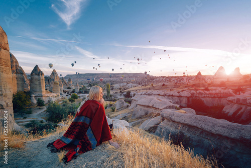 girl in ethnic clothes at dawn watching the flight a lot of balloons fly over th Canvas Print