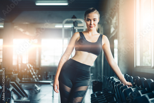 Foto op Plexiglas Fitness Young girl playing dumbbell to exercise in fitness.Slim girl lifts heavy dumbbell while training in the gym. Sports concept fat burning and a healthy lifestyle.