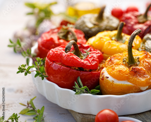 Fototapeta Roasted bell pepper with mushroom, rice, cheese and herbs filling in a baking dish on a white wooden table, close-up. A healthy and delicious vegetarian food. obraz
