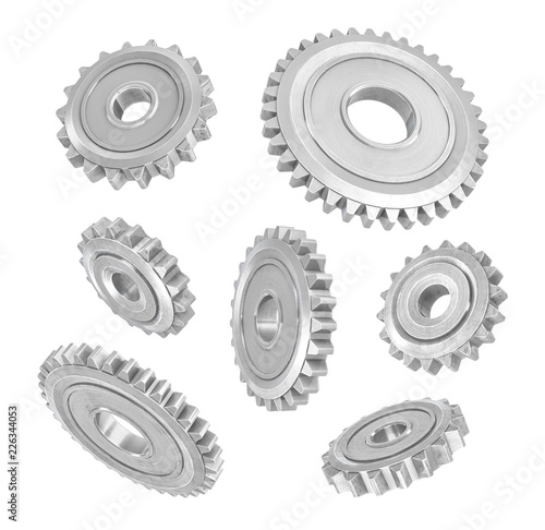 Photo  3d rendering of several metal spur gears hanging in different angles on a white background