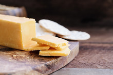 Block Of Cheddar Cheese And Slices Over A Rustic Background.. Extreme Shallow Depth Of Field With Selective Focus On Cheese. Water Crackers In  Blurred Background.