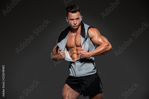 Fototapety, obrazy: Young handsome athlete bodybuilder, in beautiful sportswear, demonstrates abdominals, against a dark background. Concept - power, beauty, biceps, triceps, sports equipment, gym, sports nutrition.