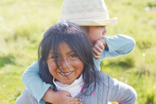 Native American Girl Holding Her Little Sister In The Countryside.