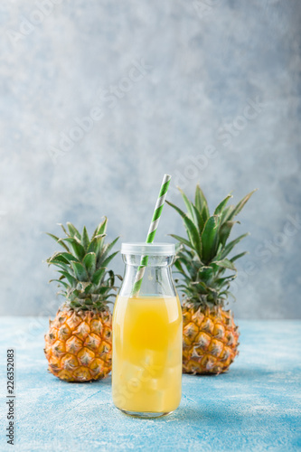 Fotobehang Cocktail Fresh pineapple juice and ripe pineapple on grey background