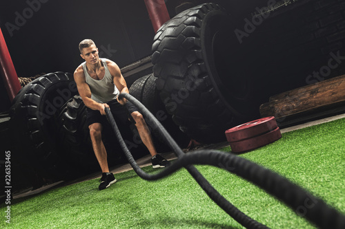 Fotografía  Man is making battle rope exercises during his cross training workout