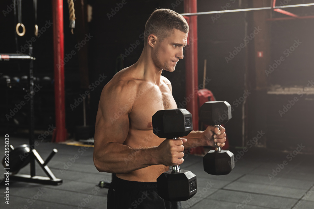 Fototapeta Young handsome bodybuilder during his arm workout in the gym