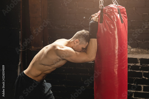 Fighter is very tired during his workout with a punching bag