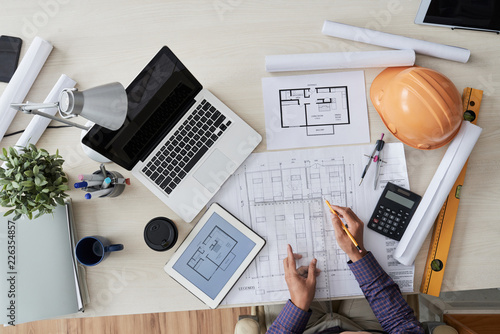 Obraz Construction engineer working with various blueprints on his table, view from above - fototapety do salonu