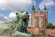 Leinwanddruck Bild - Tower spires over lion bronze sculpture guard at the entrance of Rosenborg Castle, built in 17th century. Historical landmarks of Copenhagen, Denmark