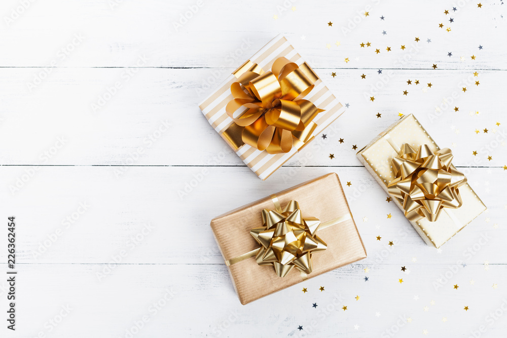 Fototapeta Heap of gift or present boxes and stars confetti on white wooden table top view. Flat lay composition for birthday, christmas or wedding.