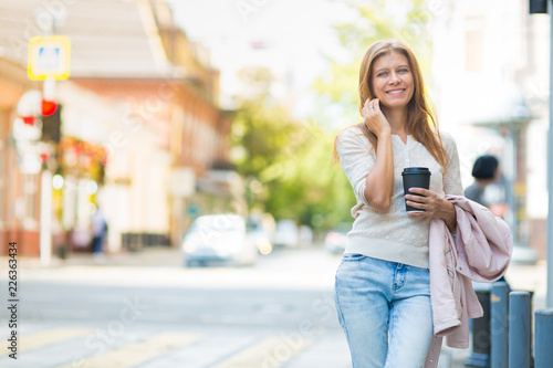 woman 30 years old walking in the city on a sunny day with a cup of hot coffee Wallpaper Mural