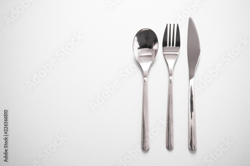 metal silverware of fork knife spoon for eating meal in restaurant grey background