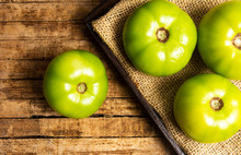 Green Tomato On A Rustic Wooden Table