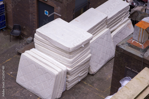 Stack of old and used mattresses left outside the back of a ...