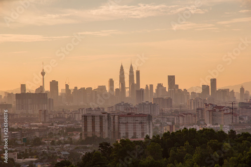 Kuala Lumpur cityscape at golden hour taken from a high viewpoint over looking the business district of the city and surrounding suburbs and hills