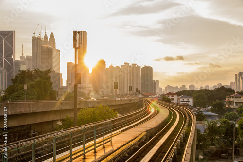 Railway tracks lead commuters to work in the busy finance and commercial centre of the Asian city of Kuala Lumpur as the sun sets between the skyscrapers in the morning
