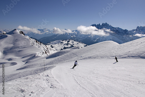 Fototapeta  Skiers in French Alps carve turns as they make their way down a piste in Avoriaz, Portes du Soleil ski area