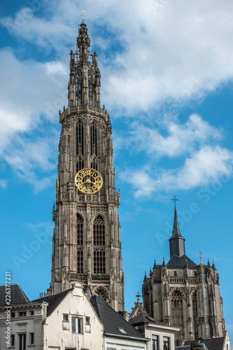 Keuken foto achterwand Antwerpen Antwerp, Belgium - September 24, 2018: Closeup of Towers of Onze-Lieve-Vrouwe Cathedral of Our Lady in back under blue cloudy sky. Parts of white facades up front.