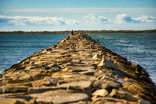 A breakwater made of rocks make s an ideal fishing pier Canvas Print