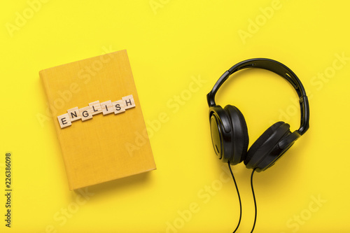 Book with a yellow cover with text English and black headphones on a yellow background Canvas-taulu