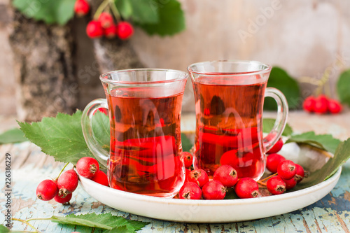Hot tea from hawthorn berries in transparent glasses on a wooden table Wallpaper Mural
