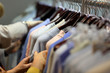 Woman chooses clothes on a hanger in the shop for sale