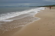Beautiful vast deserted sandy holiday beach with sea tide coming in on Norfolk coast England with tranquil ocean and blue grey sky looking across shore to land on horizon in Autumn