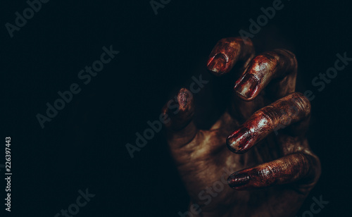 Photo  Bloody dirty zombie hand on black background